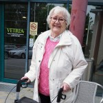 Liisa Kettunen seisoo rollaattorin kanssa ulkona ja katsoo iloisesti hymyillen kameraan.