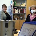 Seurakuntasihteerit Milla Suhonen ja Pirjo Myller seisovat seurakunnantoimiston pöydän takana. Pirjo Myllerillä on maski kasvoillaan.