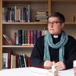 Pappi Katriina Puustinen istuu pöydän ääressä kädet pöydällä ja katsoo ikkunasta ulos. Pöydällä on kynttilä ja virsikirja, taustalla kirjahylly.