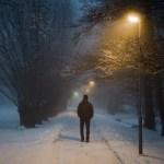 Mies kävelee lumisella tiellä puiden keskellä yksin selkä kuvaajaan päin.