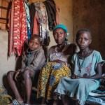 Iäkäs nainen istuu kahden lapsen kanssa afrikkalaisen kodin sängyllä ja katsoo kameraan.