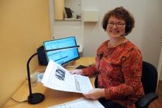 Ilona Suojama istuu työpöydän ääressä Kirkkotie-lehden sivut kädessään ja mikrofinikuulokkeet päässään, katsoo kameraan ja hymyilee. Taustalla tietokone, jossa käynnissä äänilehden äänitykseen tarvittava ohjelma.