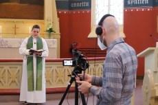 Pastori Katri Vilén seisoo Joensuun kirkon alttarilla toimittamassa jumalanpalvelusta, etualalla kansainvälisen työn ohjaaja Topi Nieminen selkäpuolelta kuvattuna, sekä videokamera, jota Topi Nieminen käyttää kuvatessaan jumalanpalvelusta suorana lähetyksenä verkkoon.