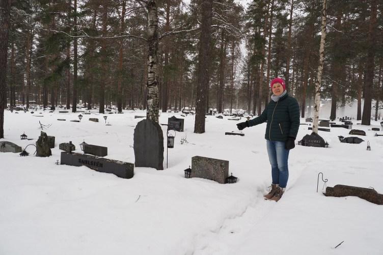 Puistopuutarhuri Eeva Laurikainen seisoo maaliskuisella Joensuun hautausmaalla ja viittilöi hautakivien puoleen.