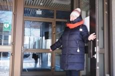 Joensuun seurakuntaneuvoston jäsen Tiina Sotkasiira seisoo hymyillen Joensuun seurakuntakeskuksen avoimella ovella ja viittilöi käsillään ihmisiä tervetulleeksi sisään.