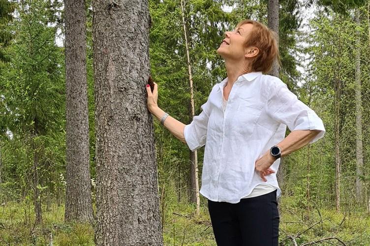 Päivi Franssila seisoo metsässä puuhun nojaten ja katselee hymyillen sen latvuksiin.