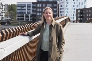 Nainen nojaa sillankaiteeseen. Takana näkyy kerrostaloja.