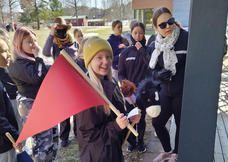 Joukko nuoria seisoo Vaivion kurssikeskuksen pihalla lukemassa pylvääseen kiinnitetty kylttiä. Useilla on mukana keppihevoset, yhdellä punainen lippu.