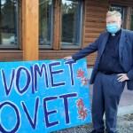 Markku Koistinen nojaa isoon Avoimet ovet -kylttiin Enon seurakuntatalon edessä avajaispäivänä.