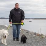 Mies taluttaa mustaa ja valkoista koiraa järven rannalla.