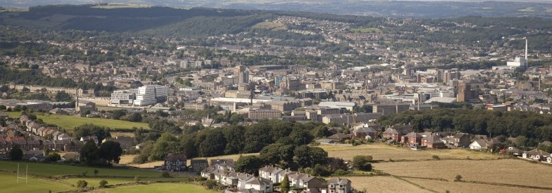 A view of Huddersfield town centre from Castle Hill. There are fields in the foreground, with a few houses, then the view in the middle is of the bustling town with many buildings large and small. In the background are more hills and countryside