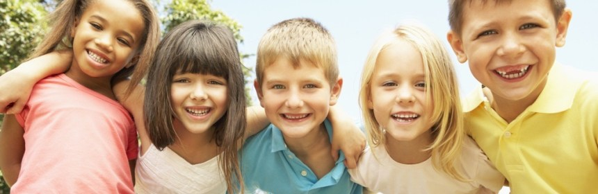 Group Of Smiling Children Relaxing In Park - foster care fortnight