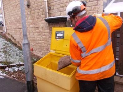 Man filling a grit bin