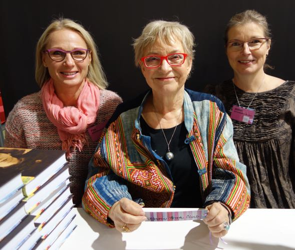 Japanista Tove 100 -näyttelyn avajaisista messuille kiirehtinyttä Tuula Karjalaista jututtuvat Kirsin Book Clubin Piia ja Minna