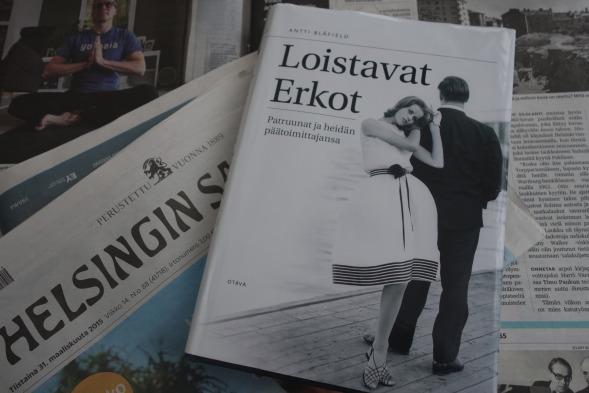 """Antti Blåfield perustelee Loistavat Erkot -kirjan kansikuvaa mm. näin: """"kustantaja on aina läsnä mutta silti sivussa."""" Kuvassa selin on Aatos Erkko ja nuosi nainen on ensimmäisen Me Naiset -lehden mallikilpailun voittaja 17-vuotias Hellevi Keko."""