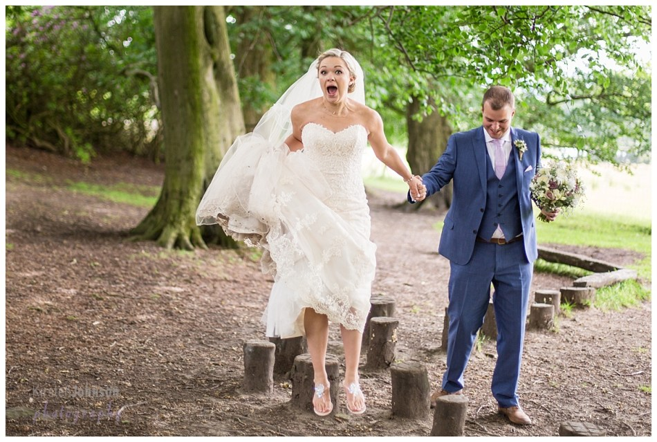 bride jumping off stump with groom holding hand