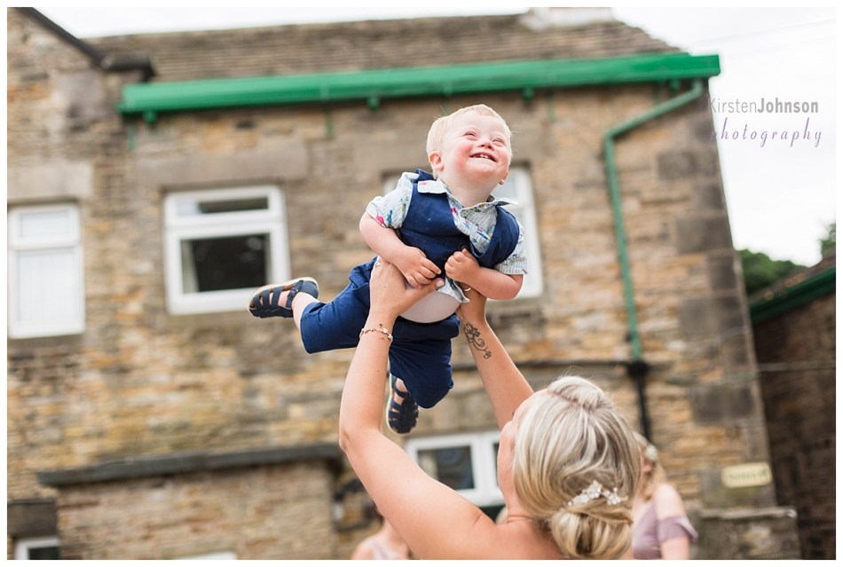 boy being lifted in air by bride