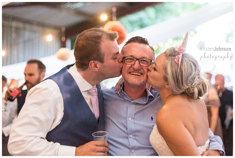 Bride and groom kissing guest on cheeks