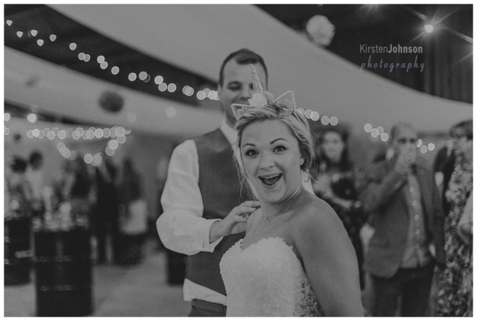 Bride laughing at camera with groom behind her