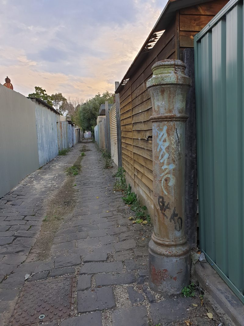 A bluestone laneway in Melbourne, surrounded by high fences