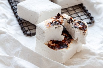 a stack of homemade marshmallows a couple of them are toasted one is torn open