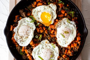 Sweet potato breakfast hash in a big cast-iron pan with over easy eggs on top