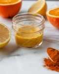 Citrus Turmeric Immunity Shot surrounded by lemons and oranges and turmeric