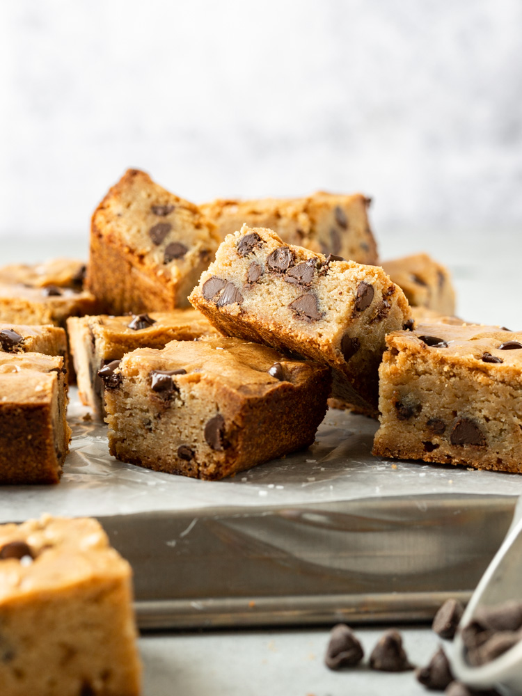 A stack of brown butter blondies with chocolate chips on a cookie sheet