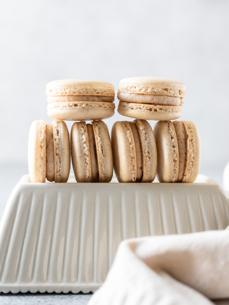 A stack of apple pie macarons on a dish