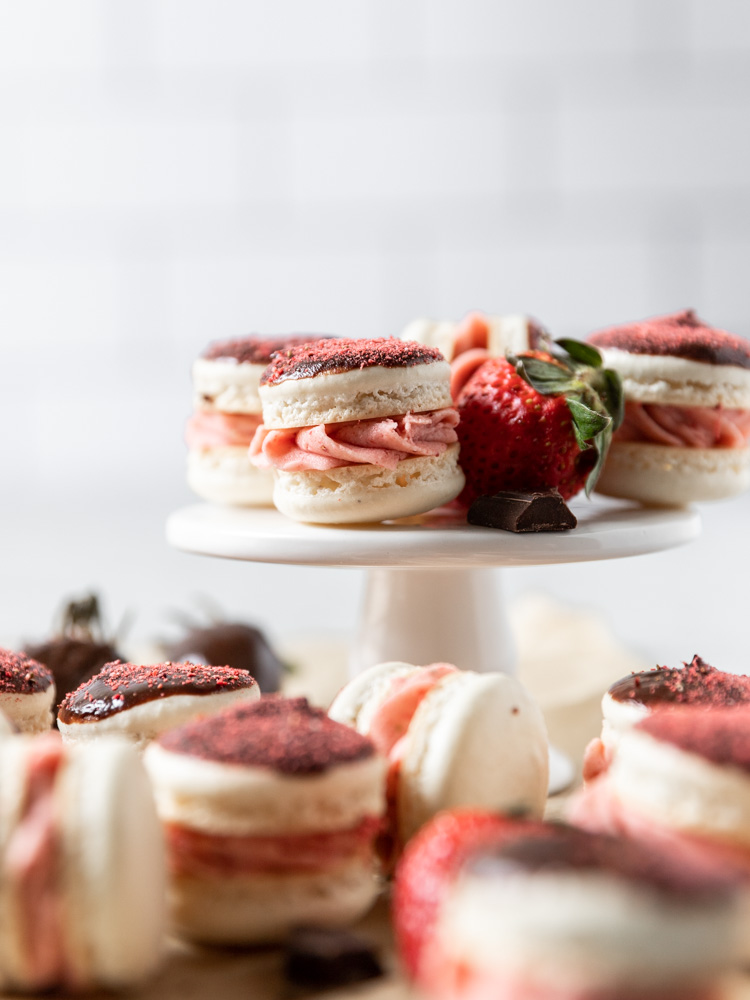 chocolate strawberry macarons on a small pedestal