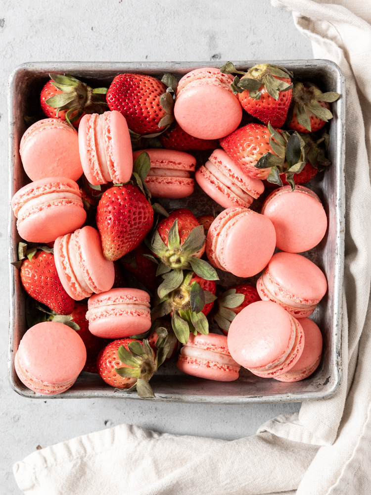 A tray of fresh strawberries and macarons