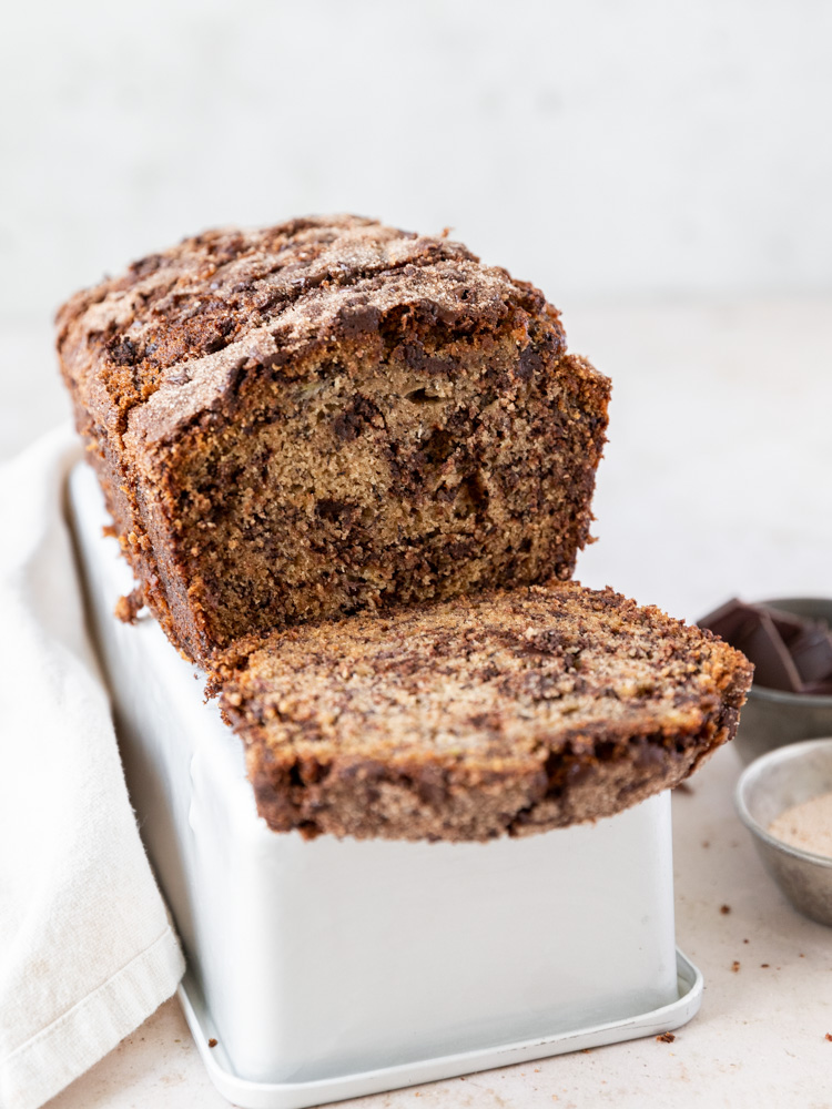 Banana bread sitting on an upside down bread pan. you can see the swirls of chocolate inside the banana bread
