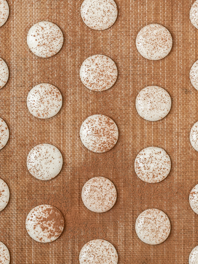 The macarons piped onto a baking sheet and dusted with cocoa powder