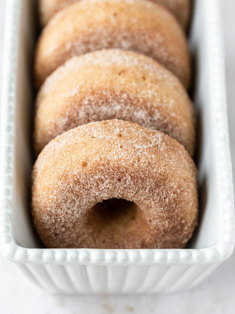 A pan with a row of baked donuts inside
