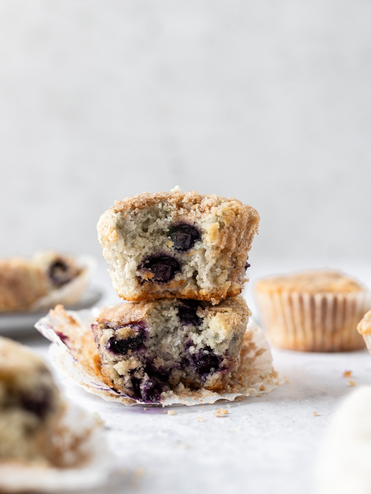 A stack of gluten-free blueberry muffins, each has a bite out of it