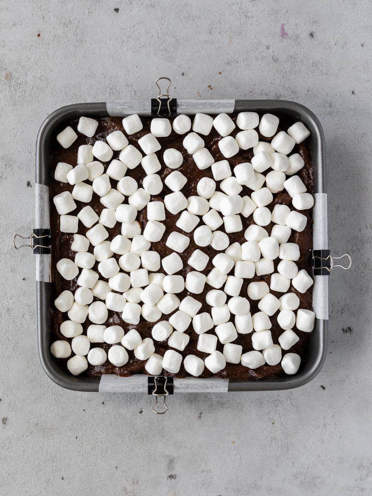 Mini marshmallows sprinkled on top of the brownie batter