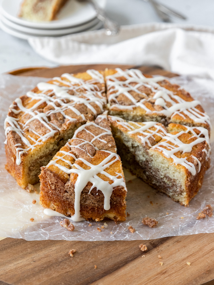 A coffee cake that is topped with maple glaze and missing a slice