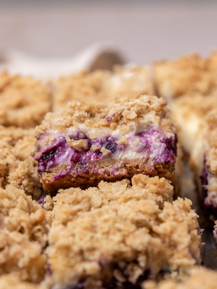 A blueberry crumble cheesecake bar propped up on other bars