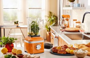 A kitchen featuring a KitchenAid® Blender in Honey filled with garlic, oil and other herbs.