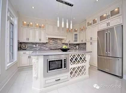 White kitchen renovation with custom cabinets, lighting, countertops and backsplash