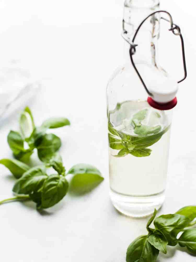 Fresh basil leaves in a glass bottle of simple syrup to make Cherry Basil Sorbet