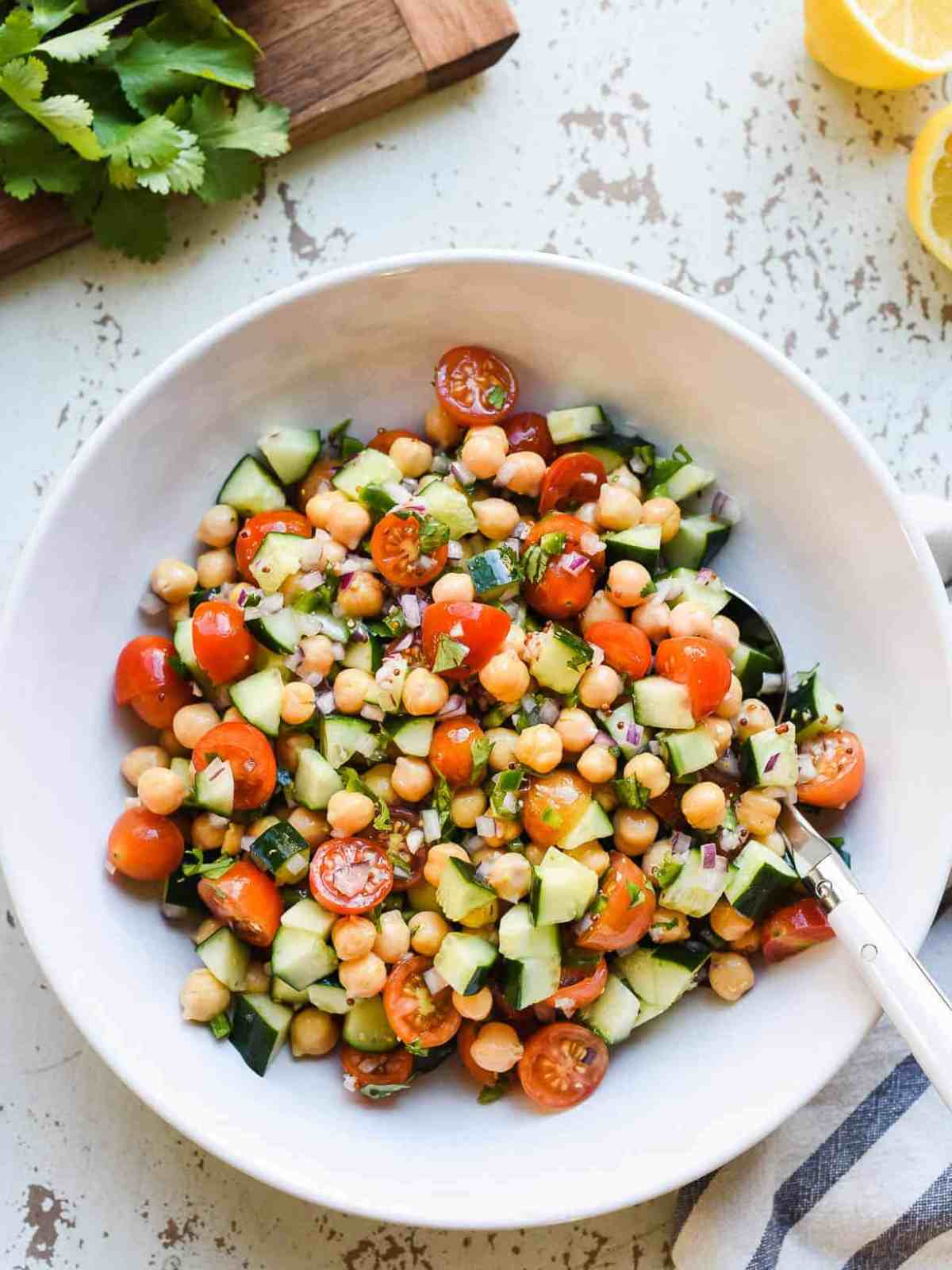Chickpea Salad with tomatoes and cucumbers in a white bowl on a light background