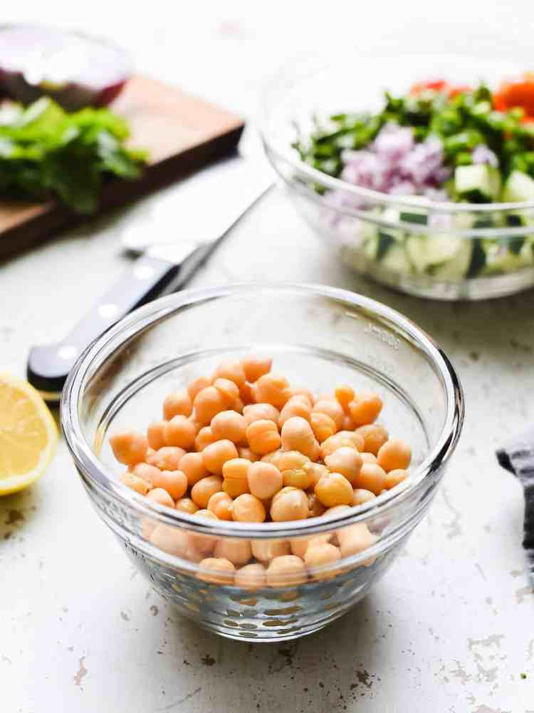 shelled chick peas in a glass bowl on a white background with salad ingredients in the background