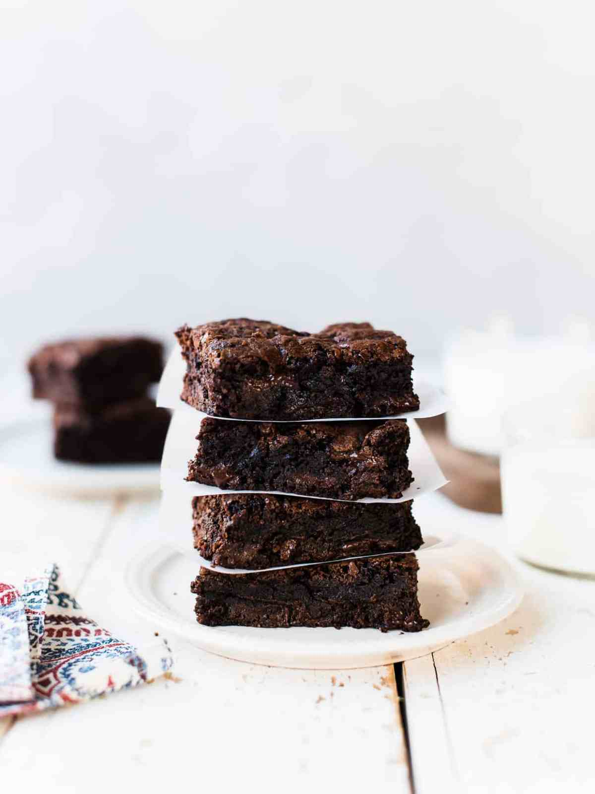Stack of gooey homemade brownies on a white plate with glasses of milk.