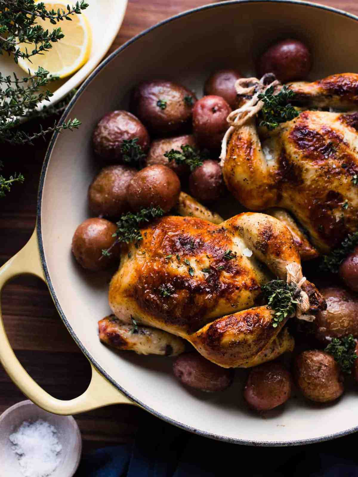 Overhead shot of roasted buttermilk brined Cornish hens on a bed of red potatoes and thyme.