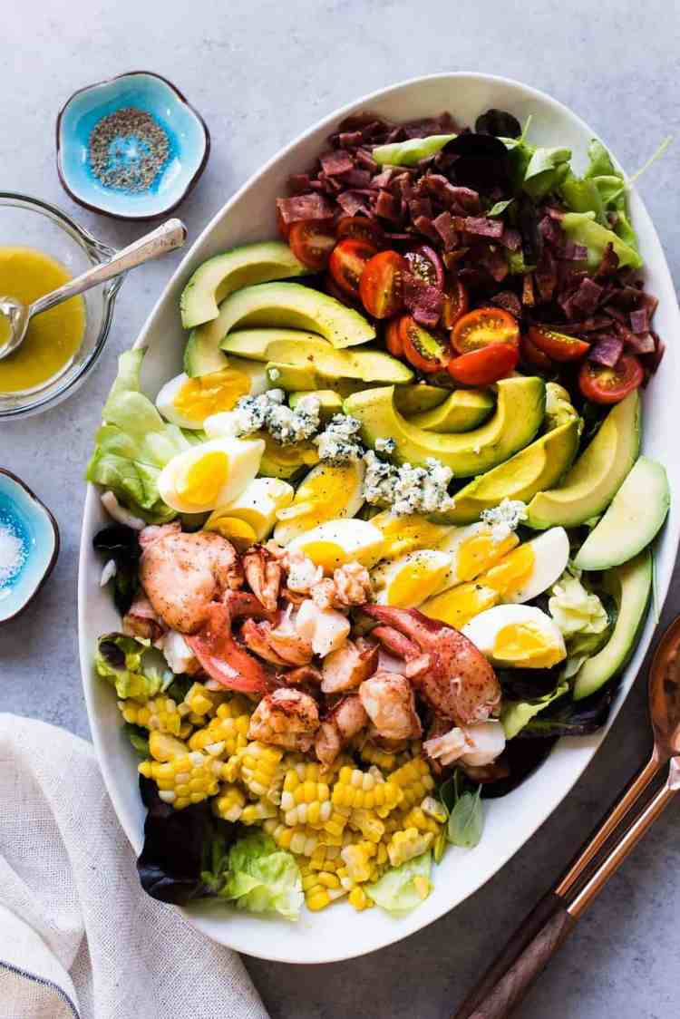 Lobster Cobb Salad on a white platter with lobster, hardboiled eggs, avocados, corn, and fresh greens.