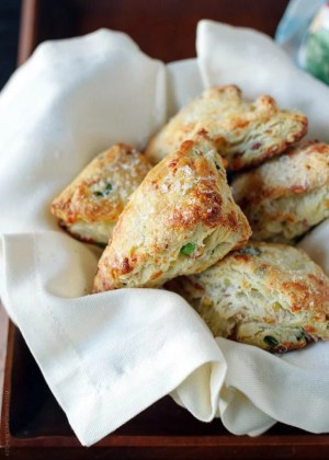 Savory Scones with Gruyere, Prosciutto and Green Onion in a basket with a white napkin