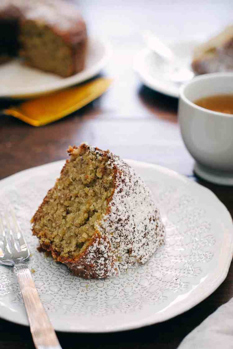 Slice of Banana Pineapple Cake with powdered sugar on a white plate. A cup of tea in the background with banana pineapple cake.