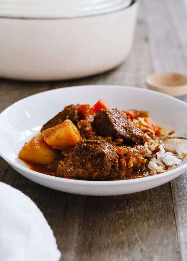 Mechado - Filipino Beef Stew with beef and potatoes in a white bowl on a wooden background