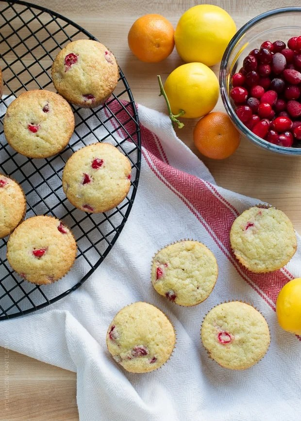 Cranberry Citrus Muffins arranged on a cooling rack and a kitchen towel, ready to eat.